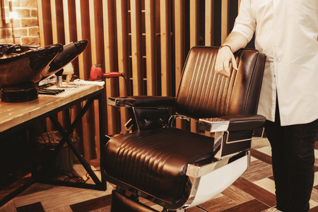 Client stylish retro vintage hairdresser chair. Barber shop for men. Desk with tools