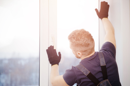 Male builder installs and checks plastic windows in apartment house.
