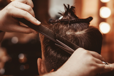 Hairstylist hands close up. Man makes fashionable haircut in Barber shop Stock Photo