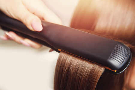 Close up Pulling strands of hair with professional ultrasonic iron tool. Spa care. Keratin straightening and restoration. Stock Photo