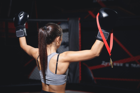 Strong woman champion MMA stands sideways back short sports top in ring with his hands up black Boxing gloves, proudly holding gold medal on red ribbon for first place, bright light spotlights Stock Photo