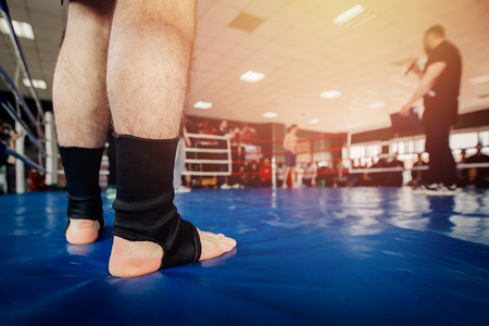 MMA fighter prepares to fight in ring, close-up legs in socks Stock Photo