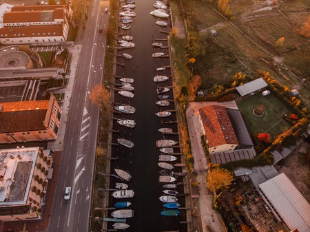 Top view of pier, road, water channel, many boats, yachts. On one hand, green Park, other urban areas, warm photos fall colors, red tile roofs contrast with white houses Stock Photo
