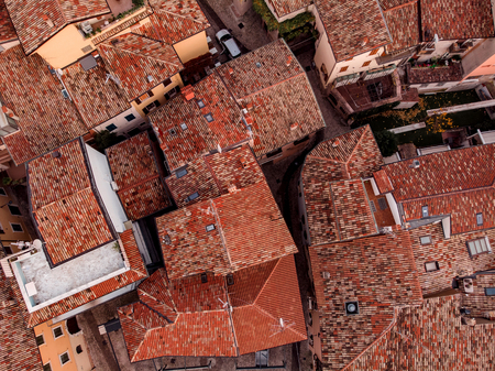 Top view tight-standing houses with narrow streets, small courtyards, Windows in neighborhood, roofs of red tiles.