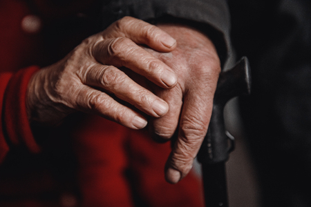 Mature couple concept. Hands of an old woman and man holding cane, skin wrinkled.
