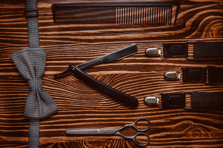 Hairstylist accessories on luxury wooden top view background. Concept barbershop.