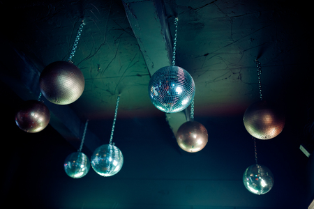 Disco ball fixed to the ceiling, dark background night party.