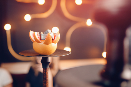 Hookah shisha with tobacco and coals on orange fruit in nightclub or bar.