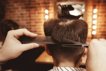 Young guy back with ponytail on his head makes haircut in men hairdresser barber shop