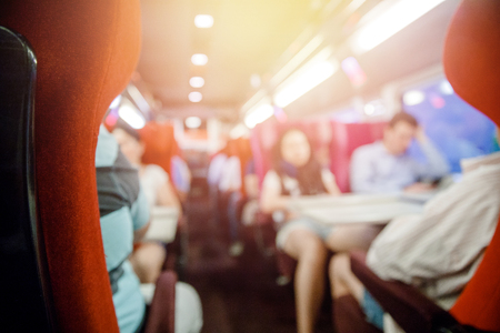 Salon of public transport bus or train with passengers, blurred background. Imagens - 116631409