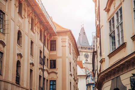 Narrow European street, houses with red tiled roofs, leads to Gothic clock tower. white sky