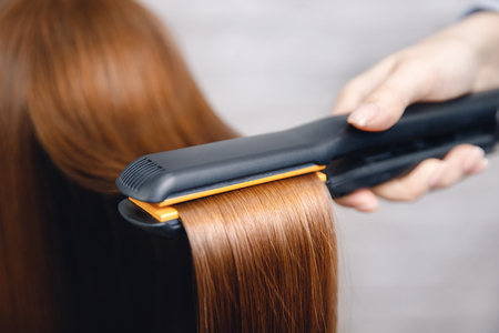 Girl does straightening of long shiny red hair with iron in beauty salon
