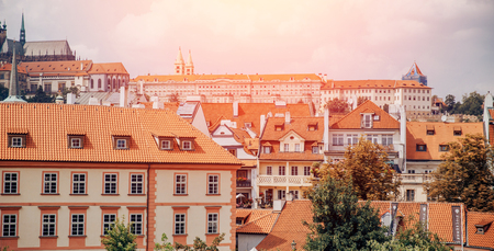 Urban landscape, European architecture of old town, houses with pitched roofs bright orange tiles, yellow foliage trees against cloudy sky
