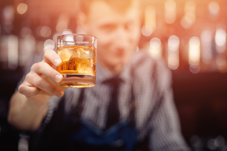 Barman serves client, gives glass of whiskey with ice double portion. Zdjęcie Seryjne