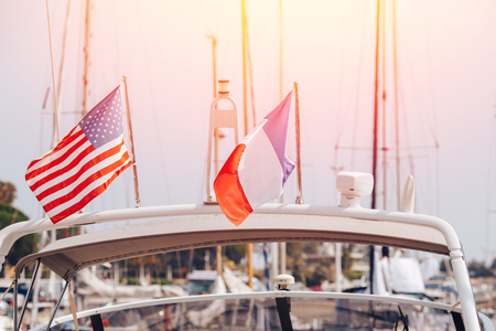 Closeup flags of France and United States on white yacht with light of sun.