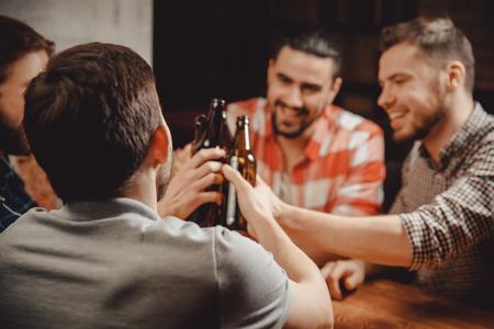 Four bearded young men old friend celebrating, celebrate narrow range in Brasserie, drinking craft beer beverages from bottles, talking toast Stok Fotoğraf