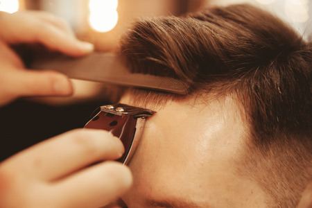 Alignment bangs on forehead of man close up in men Barber shop Stock Photo