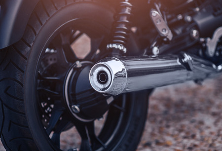 Close-up motorcycle exhaust pipe with classic wheel.