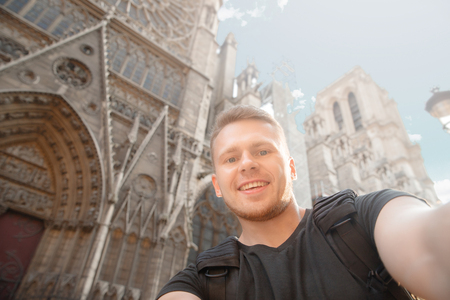 Male traveler makes selfie photo on background of building in France, Paris.