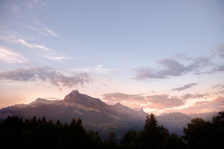 Dawn Alps mountains France, snowy peaks in fog, summer sunset.