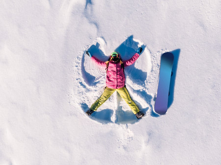 Snow angel snowboarder doing winter in bright suit. Aerial top view.