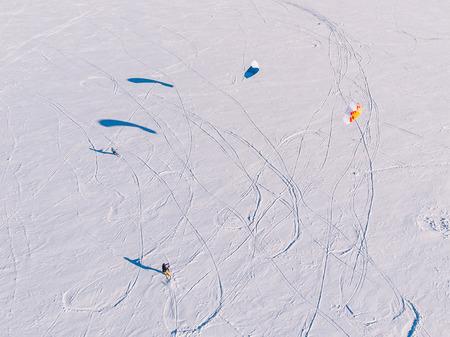 Snowkiting. Male athlete on mountain skiing with dreams kite free ride on frozen lake. Aerial view. Stock Photo
