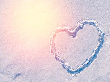 Heart symbol made of footprints in the snow, top view. Aerial photo. Stock Photo