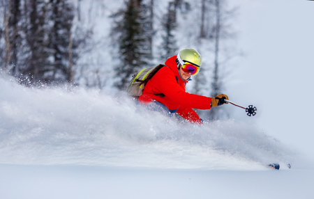 Man skier high speed rides on fresh snow and slows down, dust in air. Concept extreme winter sport.