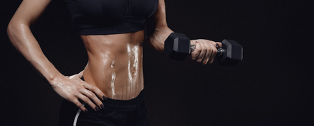 Pumped female torso with barbell in hand on black background. Copy space isolated.