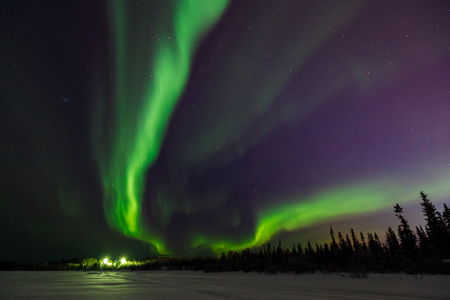 Bright green flashes of northern lights go into perspective beyond black horizon.