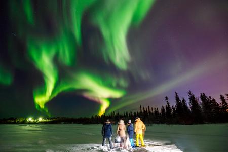 Compagnie d'amis touristiques regarde les aurores boréales à la lisière de la forêt. Effet de flou de flou artistique