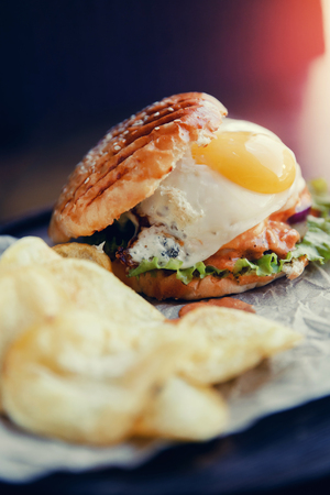Burger with fried egg, meat patty, grilled bun. Near potato chips. Concept fast food