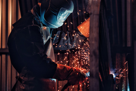 Professional welder performs welding work on metal in protective mask. Industrial worker concept.
