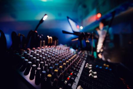 Sound equipment DJ console. Background blurred. Blue and purple colors, bright lit spotlight.