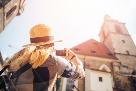 Blonde girl in straw hat, plaid shirt takes photo on phone of European stone buildings medieval architecture, her hair is covered with sun, back view Stock Photo