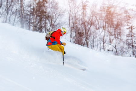 Concept extreme winter sport. Man skier high speed rides on fresh snow, dust in air. Stock Photo