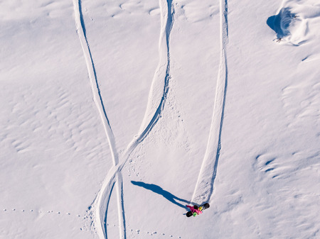 Athlete snowboarder rides off-piste clean snow snowboard, untouched in forest on slope. Aerial top view. Stock Photo