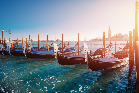 Gondolas stand in row blue-green water of Venetian canal, overexposure and glare on right, clear warm Sunny day