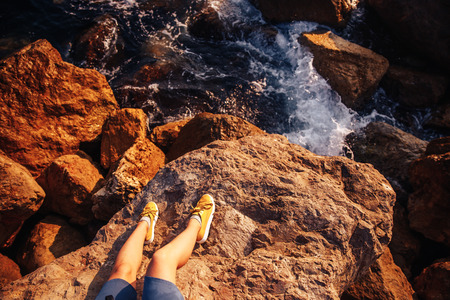 woman in blue shorts and yellow sneakers sitting on rocky cliff over raging sea Stock Photo