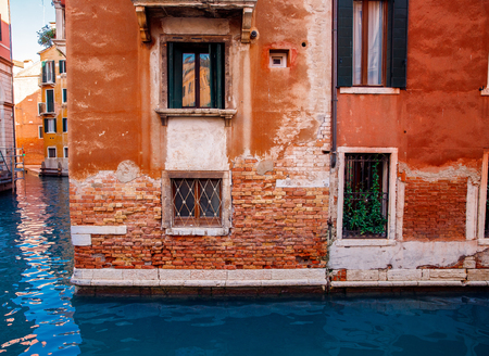 Red brick house in city on blue canal Venice, narrow water passages between buildings