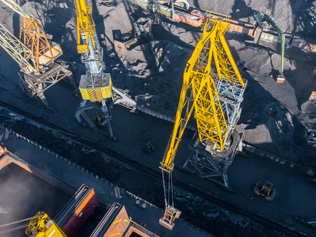 Loading coal mining in port on cargo tanker ship with crane bucket of train. Aerial top view.