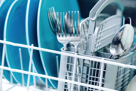 Kitchenware in dishwasher close-up, focus on basket with spoons and forks. Stock Photo