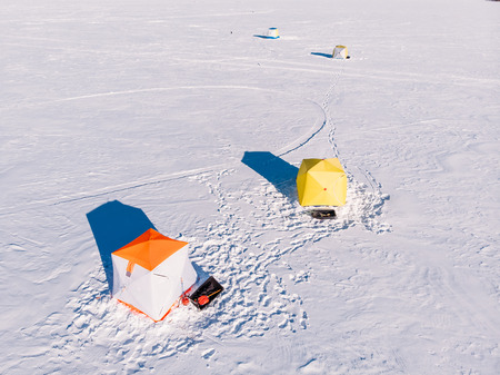 Tent for winter ice fishing, top aerial view, fisherman holding rod in hole lake. Stock Photo