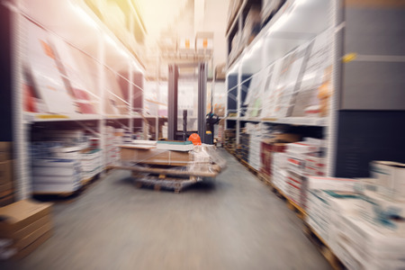 Warehouse industrial premises for storing materials and wood, forklift for containers. Concept logistics, transport. Motion blur effect. Bright sunlight.
