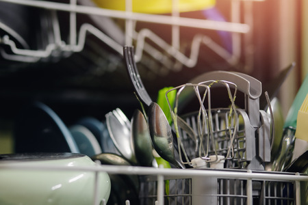 Open dishwasher with dirty dishes set for washing. Concept water saving. Stock Photo