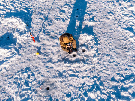 Winter fishing on ice, top aerial view, fisherman rod in hole in lake.