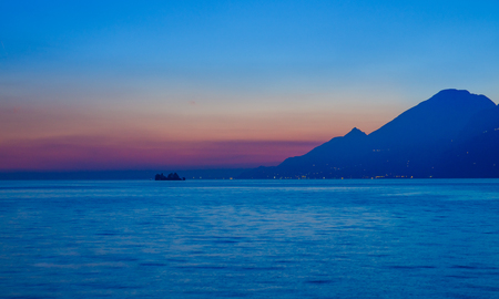 Sunset on sea, blue waters with strip of red Golden sky, huge mountain in shade