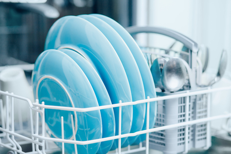Clean dishes in dishwasher close-up, background is blurred.