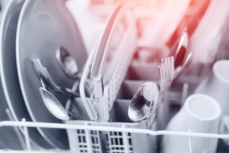 Open dishwasher with clean shine dishes and forks, spoons, cutlery. Concept water saving.