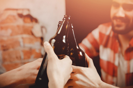 Boys in men beer bar loft style ring bottles hand close up